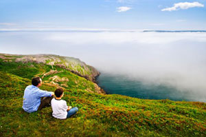 A man and boy looking out across a foggy sea towards the horizon from a green headland in Newfoundland, Canada