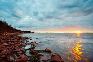 The sun setting behind the horizon, taken from the coast of Prince Edward Island, Canada